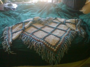 crocheted this beautiful granny square poncho. It is adult sized.  The colors are cream, country blue and desert paint (a variegated ombre).  It is made with worsted weight 100% acrylic yarn. Machine washable on the delicate cycle on cold and machine dryable on air fluff.  I am selling it for $160.00 .